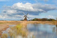 Niederländische Windmühle über blauem Himmel durch Fluss Lizenzfreie Stockbilder