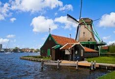 Niederländische Windmühle über Flusswassern Stockfotos