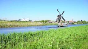 Niederländische Windmühle über Flusswassern stock footage