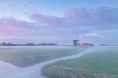 Niederländische Windmühle bei nebelhaftem Sonnenaufgang Lizenzfreie Stockbilder
