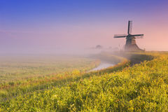 Niederländische Windmühle bei Sonnenaufgang auf einem nebeligen Morgen Stockfoto
