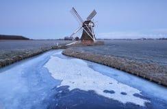 Niederländische Windmühle in der Dämmerung durch gefrorenen Fluss im Winter stockbilder