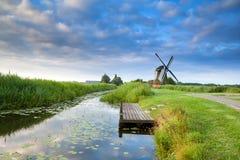 Niederländische Windmühle durch Fluss mit reflektiertem blauem Himmel Stockfotografie