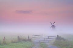 Niederländische Windmühle im dichten Nebel bei Sonnenaufgang Stockfoto