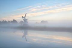Niederländische Windmühle im dichten Nebel während des Sonnenaufgangs Stockbild