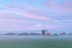 Niederländische Windmühle im nebeligen Sonnenaufgang Stockfotos