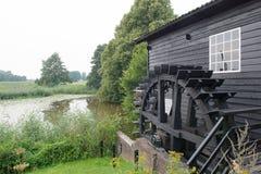 Niederländische Windmühle nahe dem Fluss Stockfotografie