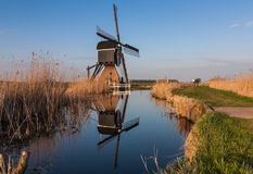 Niederländische Windmühle reflektiert im Fluss Stockfoto