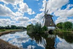 Niederländische Windmühle reflektierte sich im Wasser und im bewölkten blauen Himmel lizenzfreie stockfotos
