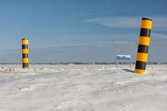 Niederländische Winterlandschaft mit schneebedecktem Ackerland und bunten Verkehrsschildern Stockfoto