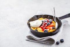 Niederländischer Babypfannkuchen mit Beeren und Creme in einer Gusseisenwanne stockbilder