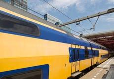 Niederländischer Doppeldeckerzug verlässt eine Station Lizenzfreies Stockfoto