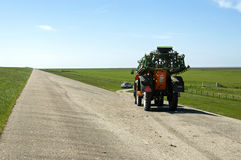 Niederländischer Landwirt, der Traktor auf Uferdamm von Nordsee fährt Lizenzfreie Stockfotografie