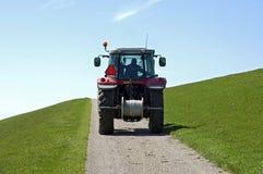 Niederländischer Landwirt, der Traktor auf Uferdamm von Nordsee fährt Lizenzfreie Stockbilder