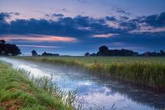 Niederländisches Ackerland mit Kanal an der Dämmerung Stockfotos