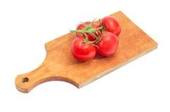 Niederlassung der roten Tomaten auf dem hölzernen Schneidebrett Lizenzfreie Stockfotos