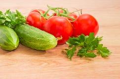 Niederlassung der roten Tomaten, zwei Gurken und der Petersiliennahaufnahme Stockfotos