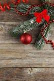 Niederlassung des Weihnachtsbaums mit Bällen auf hölzernem Hintergrund Lizenzfreies Stockbild