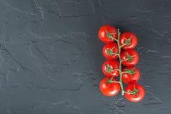 Niederlassung von kleinen Tomaten auf einem schwarzen Stein Stockfoto