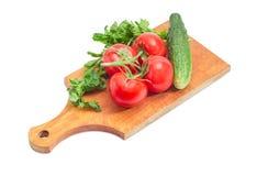 Niederlassung von Tomaten, von Gurke und von Petersilie auf Schneidebrett Lizenzfreies Stockfoto
