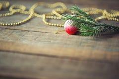 Niederlassungen der Fichte, des roten Weihnachtsballs und des Bördelns auf hölzernem Hintergrund Einladung des neuen Jahres Kopie stockfotos