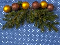 Niederlassungen der Fichte mit Weihnachtsbällen auf einem Hintergrund des blauen Stoffes in den Tupfen Stockfotos