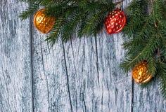 Niederlassungen der Fichte mit Weihnachtsdekorationen auf einem Hintergrund von alten Holzverkleidungen Stockfotos