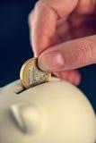 Niederlegen von einer Euromünze in piggy Münzenbank Lizenzfreies Stockfoto