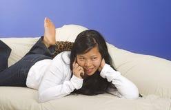 Niederlegung auf Couch mit Telefon stockfotos