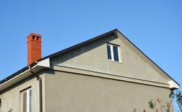 Niedokończony dom z metalu dachem, ceglanym kominem, podeszczowa rynna i obraz stock