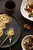 niedokończony spaghetti z sałatką, dokrętki i napój na szarości, ukazujemy się fotografia stock