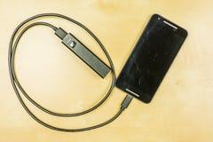 Smartphone LG Google Nexus 5 loaded with powerbank. royalty free stock photography