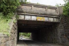 Niedrige BRITISCHE Eisenbahn/Eisenbahnbrücke mit Warnung Lizenzfreies Stockfoto
