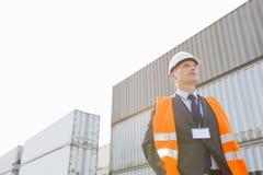 Niedrige Winkelsicht der Arbeitskraft stehend gegen Frachtbehälter in Versandyard Lizenzfreies Stockfoto