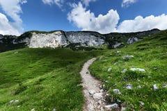 Niedrige Winkelsicht des Gebirgszugs mit Wanderweg unter bewölktem Himmel Achensee-Bereich, Tirol, Österreich Lizenzfreie Stockfotos