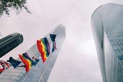 Niedrige Winkelsicht des Geschäftsgebiets mit den Flaggen, die auf foregr wellenartig bewegen Stockfoto