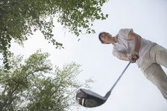 Niedrige Winkelsicht des Mannes erhalten bereit, den Golfball auf dem Golfplatz zu schlagen Lizenzfreies Stockbild
