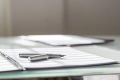 Niedrige Winkelsicht des silbernen Tintenstiftes, der auf weißem Blatt Papier I liegt lizenzfreie stockfotos