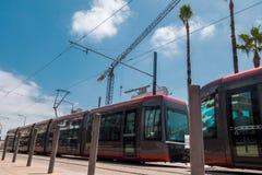 Niedrige Winkelsicht einer Tram, die nahe eine Baustelle agains überschreitet stockfotografie