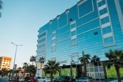 Niedrige Winkelsicht eines modernen glänzenden Gebäudes und der Autos Stockbilder