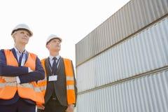 Niedrige Winkelsicht von den Arbeitskräften, die gegen Frachtbehälter stehen Lizenzfreies Stockbild