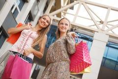 Niedrige Winkelsicht von den glücklichen zwei jungen Frauen, die mit ihren Händen angehoben stehen und die Einkaufstaschen halten Stockfotografie