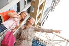 Niedrige Winkelsicht von den glücklichen zwei jungen Frauen, die mit ihren Händen angehoben stehen und die Einkaufstaschen halten Lizenzfreie Stockfotos