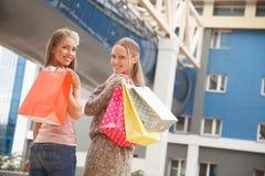 Niedrige Winkelsicht von den glücklichen zwei jungen Frauen, die mit ihren Händen angehoben stehen und die Einkaufstaschen halten Stockbild