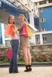 Niedrige Winkelsicht von den glücklichen zwei jungen Frauen, die mit ihren Händen angehoben stehen und die Einkaufstaschen halten Lizenzfreies Stockbild