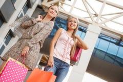 Niedrige Winkelsicht von den glücklichen zwei jungen Frauen, die mit ihren Händen angehoben stehen und die Einkaufstaschen halten Stockfoto