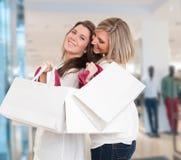 Niedrige Winkelsicht von den glücklichen zwei jungen Frauen, die mit ihren Händen angehoben stehen und die Einkaufstaschen halten Stockbilder