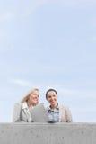 Niedrige Winkelsicht von glücklichen jungen Geschäftsfrauen mit dem Laptop, der bei der Stellung auf Terrasse gegen Himmel weg sc Stockfoto