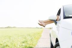 Niedriger Abschnitt der Frau entspannend im Auto auf Landstraße Lizenzfreie Stockfotos