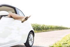 Niedriger Abschnitt der Frau entspannend im Auto auf Landstraße Lizenzfreies Stockfoto